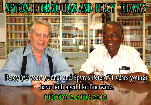 PHOTO OF SPYROS PETER GOUDAS & PERCY THOMAS memorable photograph was taken IN 2013 The Saturday Night Musical Recipe Program was on the airwaves. I have to make a parenthesis here to let you know that Peter was beginning to understand the food business. He knew his records and his music.  However, he had one deficiency, a language problem.  His English was very poor because he did not pursue English language courses. He grasped concepts and used words he picked up at the street- level, such as: Rasscloth, Bombacloth, Irie, Cha Monn.Therefore, he hired the best of the best, the cream of the crop at the time: Wynn Calendar, Jasse MacDonald, Percy Thomas and Colin Hansen, to mention a few as announcers and commentators.
