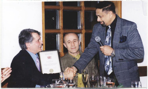 PHOTO OF KENN F. SHAH PRESENTING THE REPUBLIC OF TRINIDAD AND TOBAGO AWARD TO SPYROS PETER GOUDAS FOR HIS CONTRIBUTION TO THE CULTURE AND ARTS OF THIS TWIN ISLAND NATION.